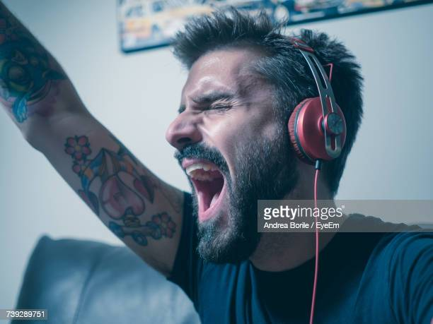 Close-Up Of Man Screaming While Listening To Music On Headphones At Home