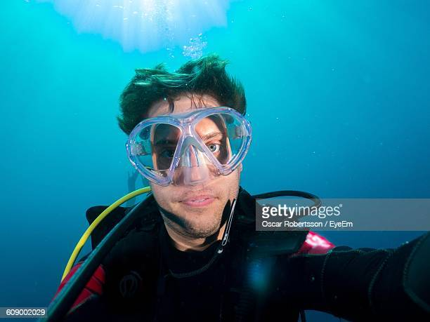 Close-Up Of Man Scuba Diving In Sea