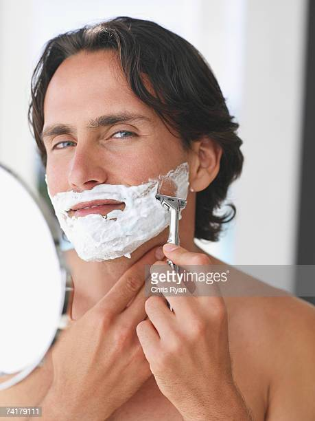 Close-up of man shaving with mirror