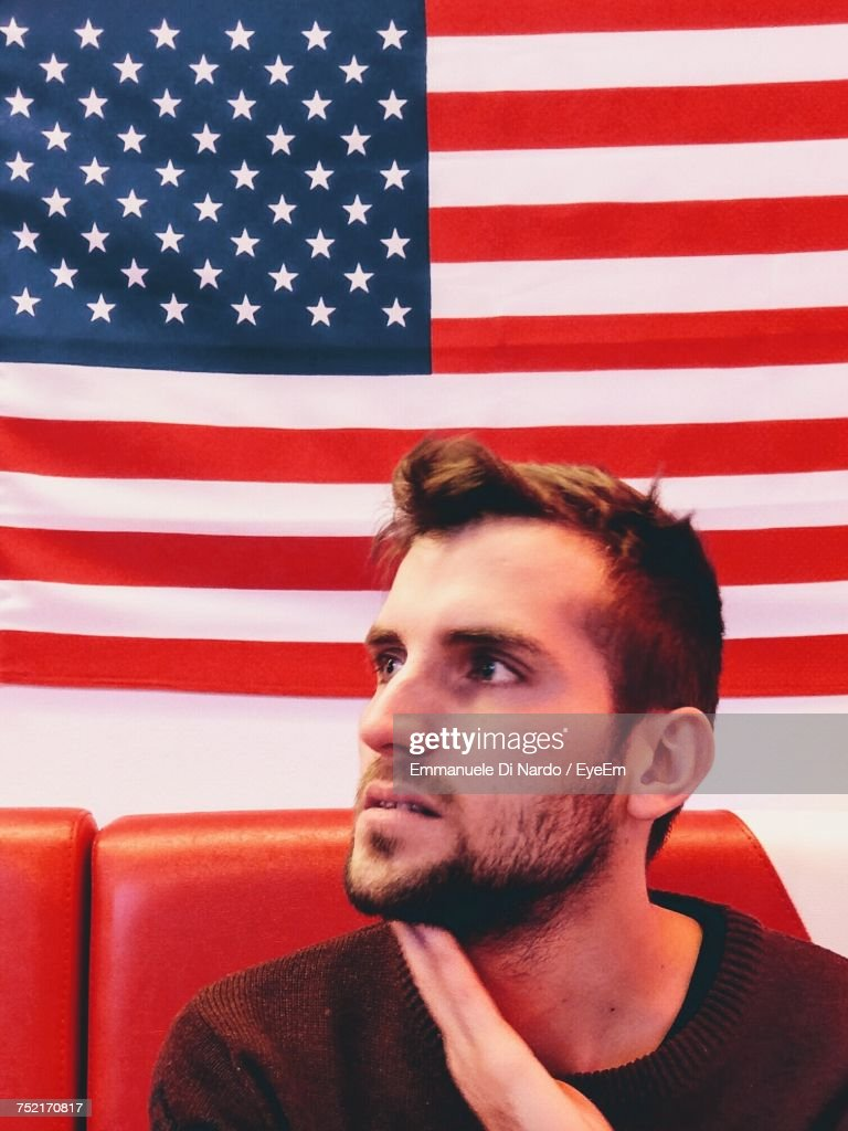 Close Up Of Man Sitting On Chair Against American Flag