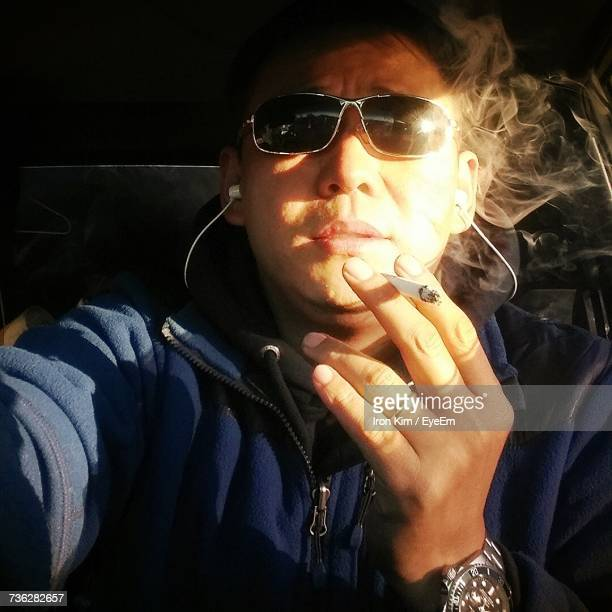 Close-Up Of Man Smoking Cigarette While Traveling In Car