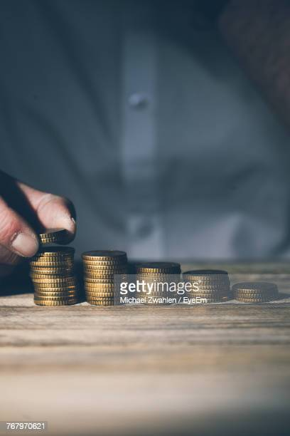 Close-Up Of Man Stacking Coins On Table