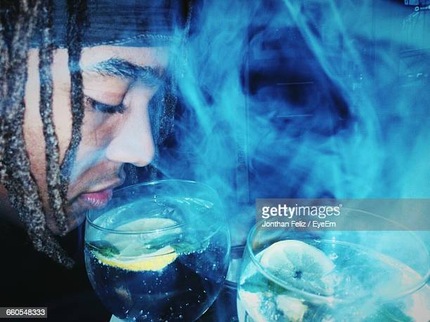 Close-Up Of Man Surrounded By Smoke Having Alcohol