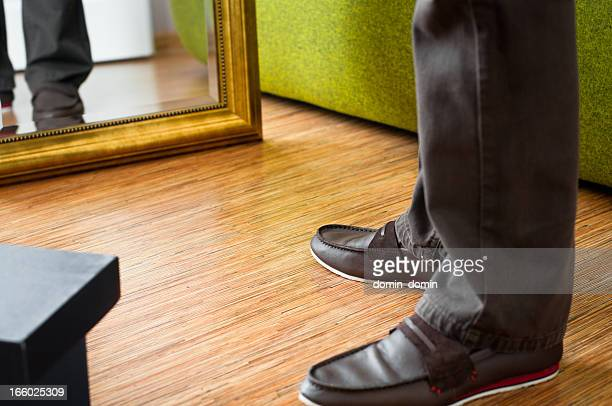 Close-up of man trying on new moccasins shoes, wardrobe interior