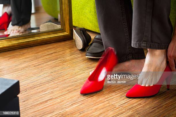 Close-up of man trying on red woman's high-heels, wardrobe interior