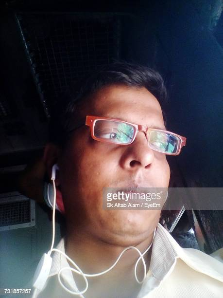 Close-Up Of Man Wearing In-Ear Phones While Traveling In Train