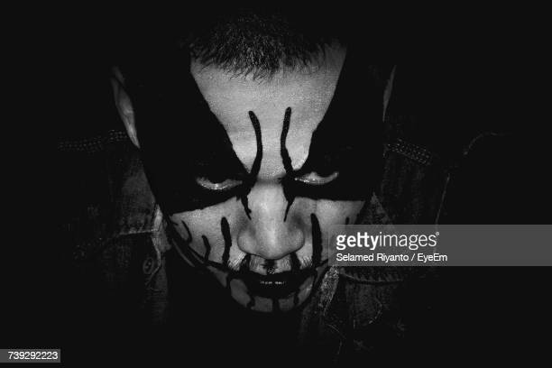Close-Up Of Man With Face Paint In Dark