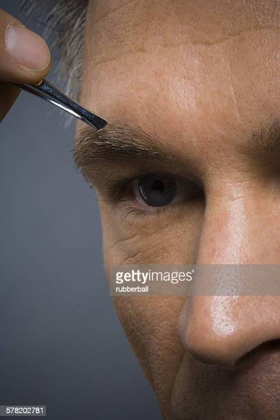 Closeup of man with tweezers plucking eyebrows