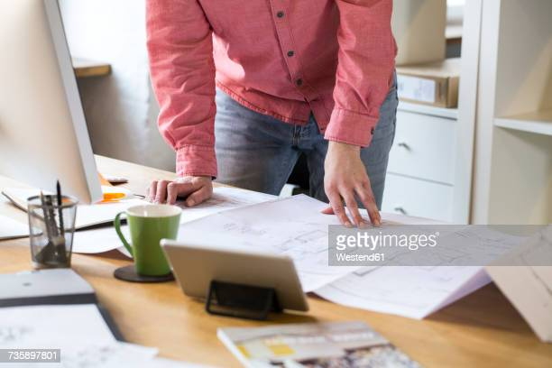 Close-up of man working on blueprint at desk in office