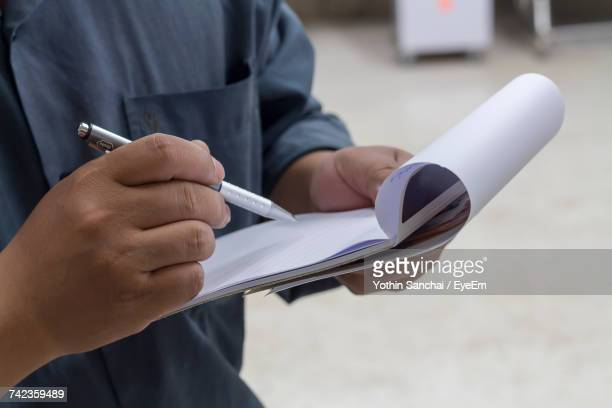 Close-Up Of Man Working On Paper