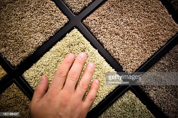 Close-up of man's hand feeling carpet samples