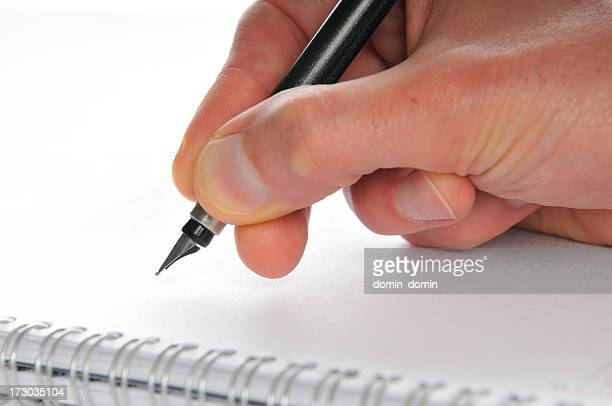Close-up of man's hand making notes, spiral notepad, blank page