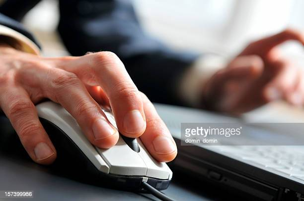 Close-up of man's hand on computer mouse, working on laptop