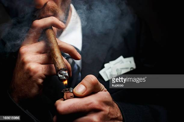 Close-up of man's hand with cigar and lighter