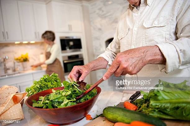 Close-up of man's hands tossing salad