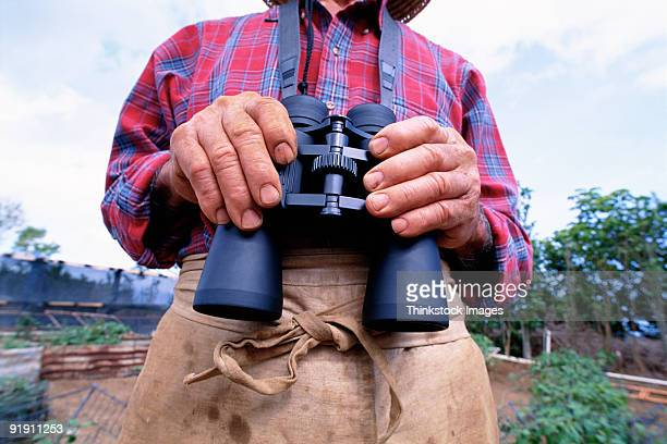 Close-up  of mans torso with his  hands holding a pair of binoculars that hanging on strap around his neck
