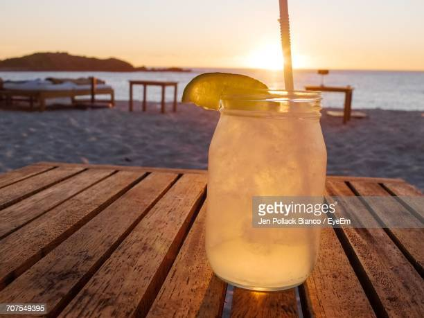 Close-Up Of Margarita On Wooden Table At Beach During Sunset