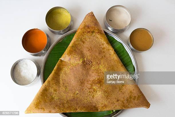 Close-up of Masala Dosa served on steel plate with  banana leaf underliner