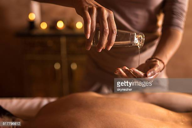 Close-up of massage therapist pouring massage oil in hand.