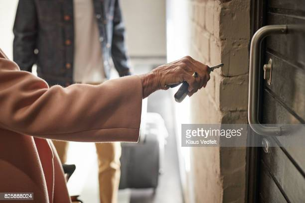 Close-up of mature couple opening door to holiday rental apartment with key
