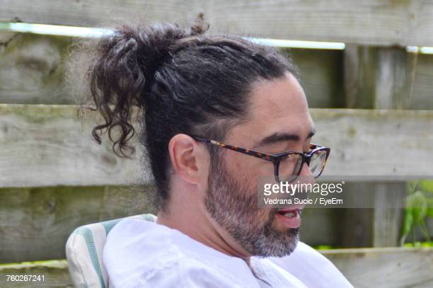 Close-Up Of Mature Man With Hair Bun Wearing Eyeglasses By Fence