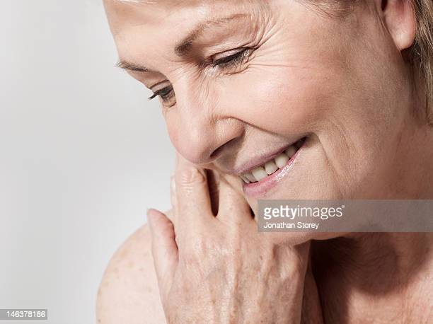 Close-up of mature woman smiling, hand in shot