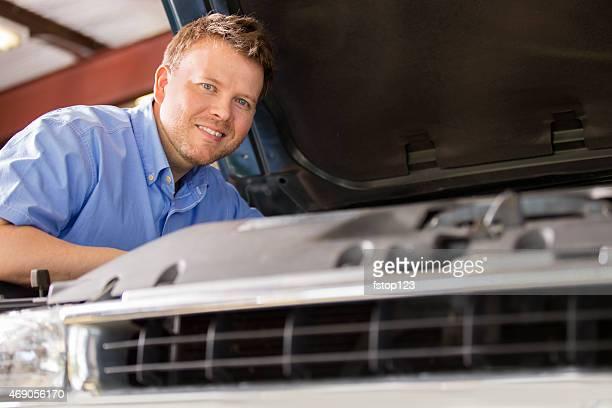 Primer plano de mecánico trabajando en vehículo de motor. Tienda de reparaciones.