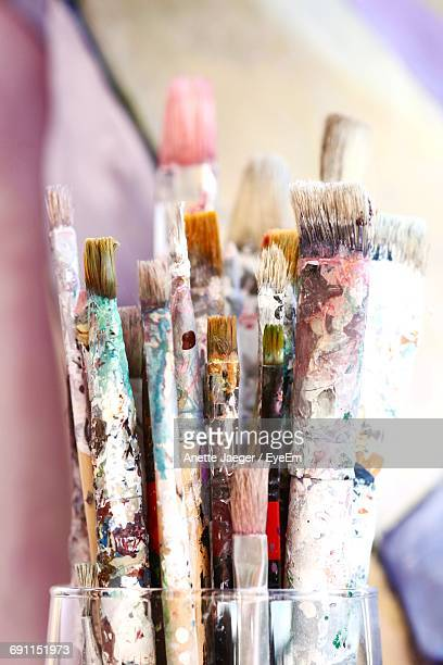 Close-Up Of Messy Paint Brushes At Table