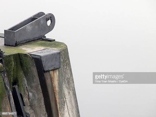 Close-Up Of Metal Attached To Wooden Post Against White Background