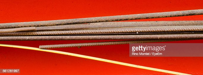 Close-Up Of Metal Rods On Red Background