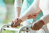 Close-up photo of patient's hands placed on metal walker