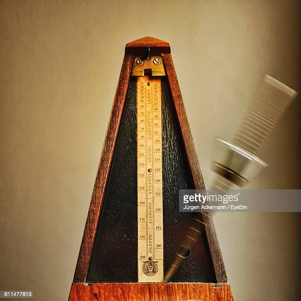Close-Up Of Metronome Against Wall