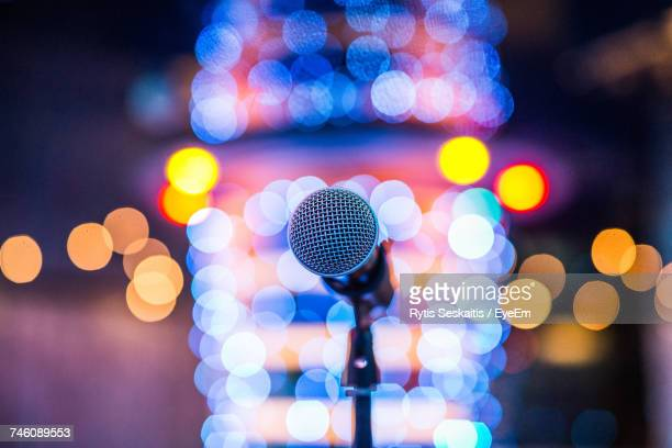 Close-Up Of Microphone Against Abstract Lights