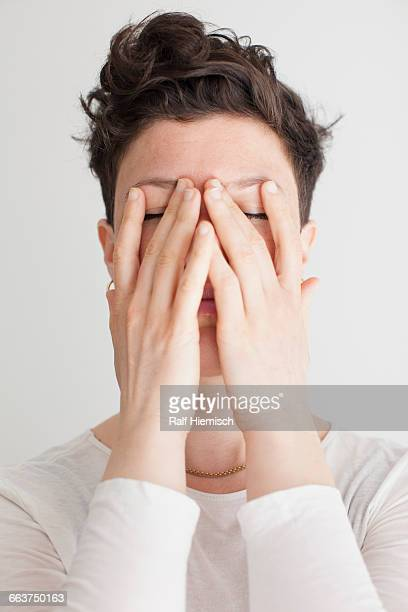 Close-up of mid adult woman covering her face with hands