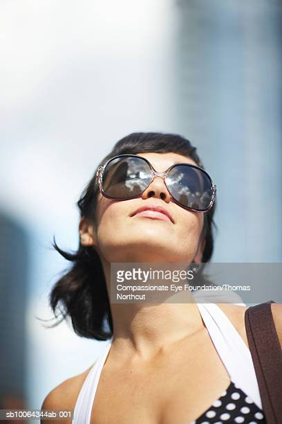 Close-up of mid adult woman in retro sunglasses looking up