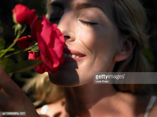 Close-up of mid adult woman smelling rose in garden, eyes closed