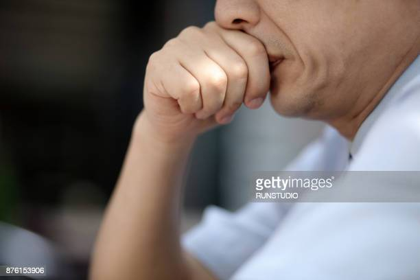 close-up of middle- aged man thinking with hand on mouth