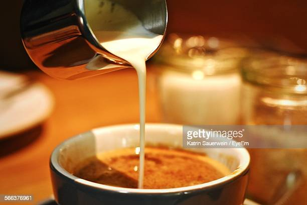 Close-Up Of Milk Pouring In Coffee On Table