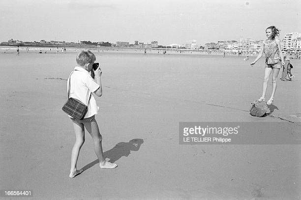 CloseUp Of Minou Drouet Aux Sables d'Olonne sur la plage un jeune garçon en chemisette photographiant l'enfant prodige Minou DROUET aujourd'hui âgée...