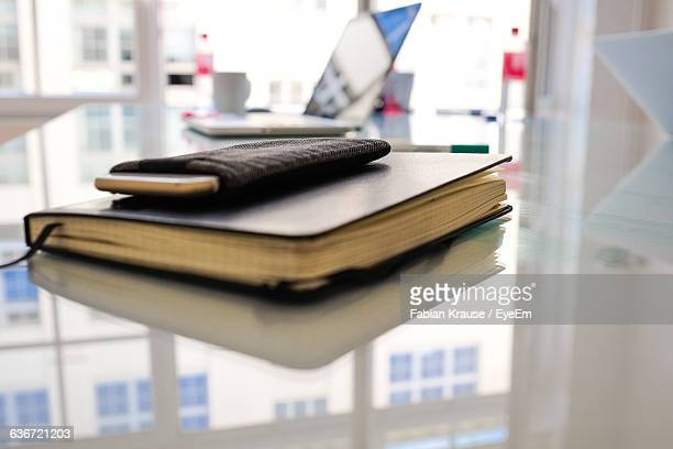 Close-Up Of Mobile Phone In Cover On Diary At Desk