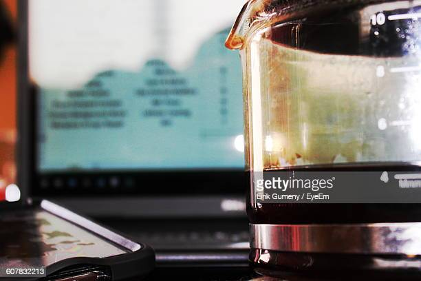 Close-Up Of Mobile Phone With Coffee Maker On Table