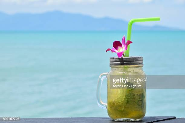 Close-Up Of Mojito Cocktail In Glass Jar On Table Against Sea