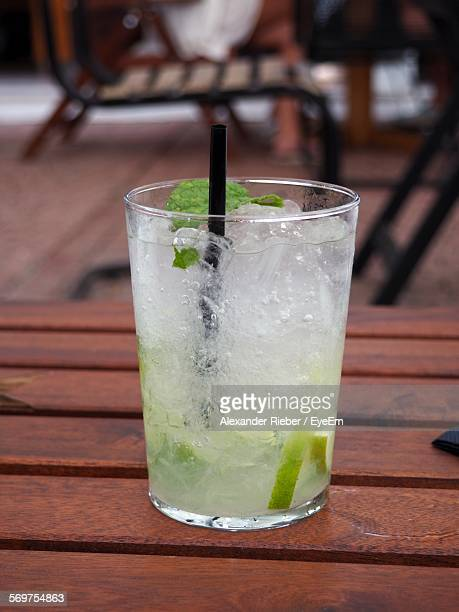 Close-Up Of Mojito With Straw On Wooden Table