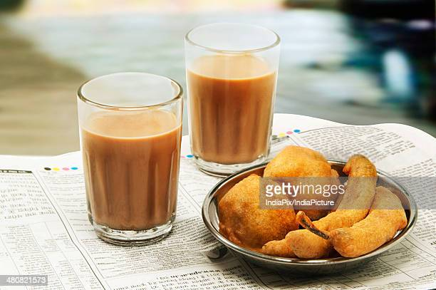 Close-up of morning chai with bhajiyas and vada on newspaper