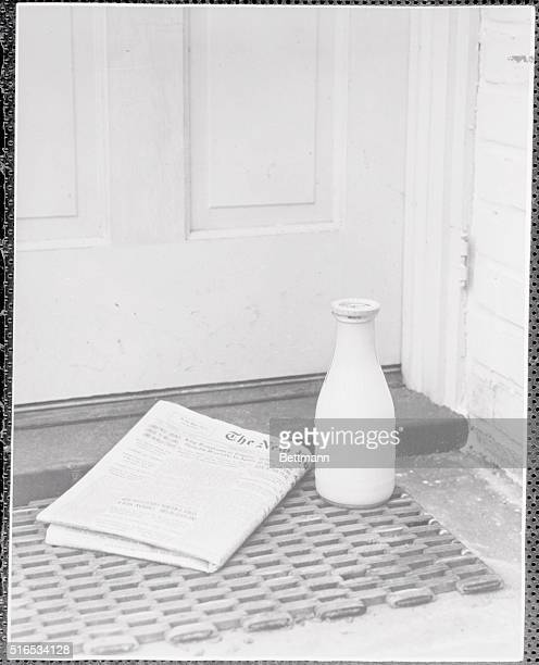 Closeup of morning paper the 'New York Times' and bottle of milk on doorstep Undated photograph