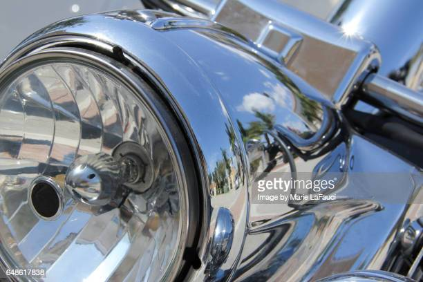 Close-up of motorcycle headlight mirror reflection