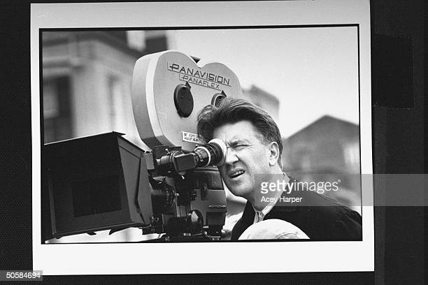 Closeup of movie director David Lynch looking through Panavision Panaflex movie camera as he directs filming of Wild at Heart on street location