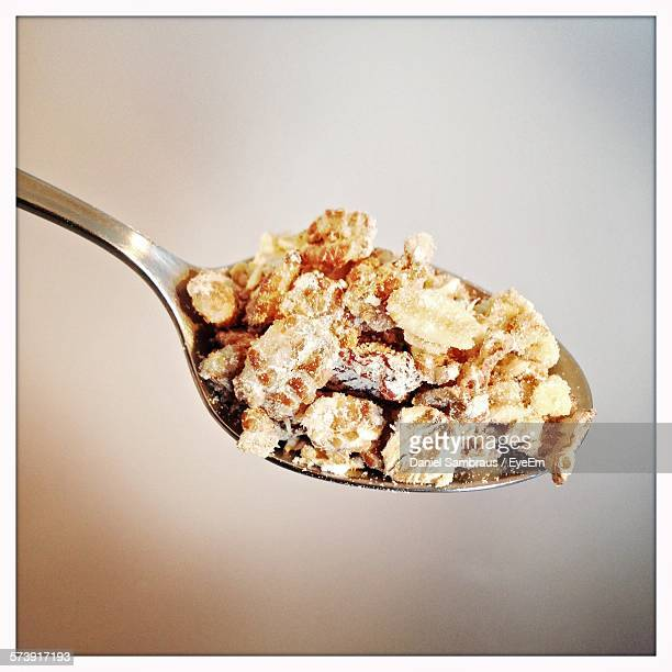 Close-Up Of Muesli On Spoon Against Colored Background
