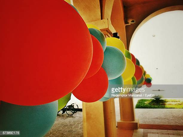 Close-Up Of Multi Colored Balloons Tied To Building Column