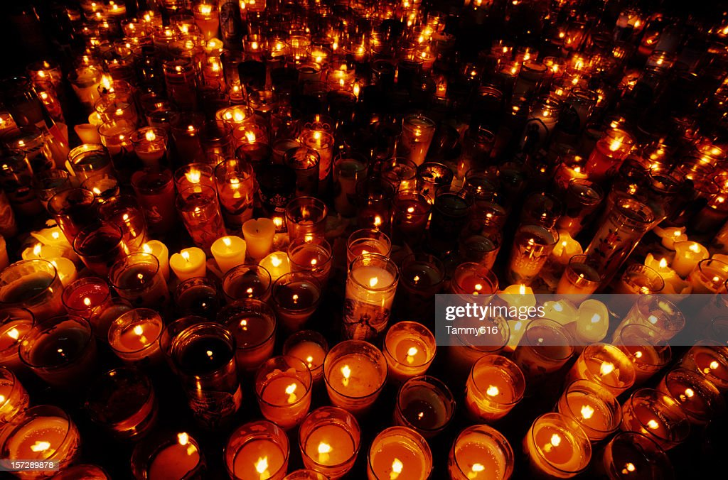 A close-up of multiple candles in a vigil